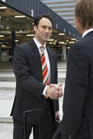 Businessmen shaking hands in airport 11029002465  写真素材・ストックフォト・画像・イラスト素材 アマナイメージズ