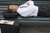 Businessman sleeping on a park bench