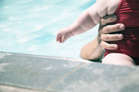 Man helping baby swim