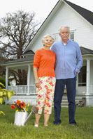 Senior couple standing in front of house