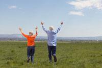 Senior couple running through fields 11029002634| 写真素材・ストックフォト・画像・イラスト素材|アマナイメージズ