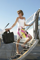 Young woman boarding airplane
