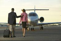 Businesspeople walking towards airplane