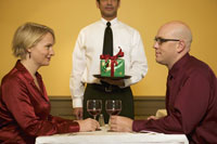 Waiter serving gift to couple