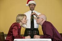 Waiter holding mistletoe for couple