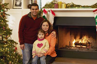 Family smiling beside fireplace