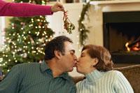 Woman dangling mistletoe between couple