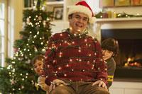 Children tying man up in Christmas light