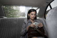 Woman counting money in backseat of taxi