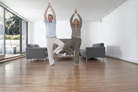 Middle-aged couple practicing yoga