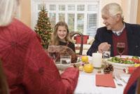 Girl smiling during Christmas dinner 11029003181| 写真素材・ストックフォト・画像・イラスト素材|アマナイメージズ