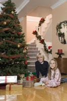 Children sitting by Christmas tree