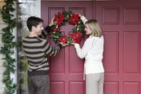 Couple hanging Christmas wreath 11029003199| 写真素材・ストックフォト・画像・イラスト素材|アマナイメージズ