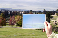 Woman holding photo over landscape