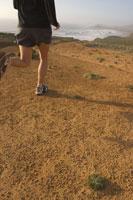 Jogger on dirt road 11029003351| 写真素材・ストックフォト・画像・イラスト素材|アマナイメージズ