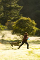 Woman running with dog in countryside