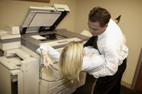 Businesspeople dancing by copy machine
