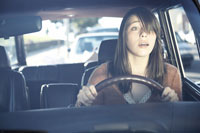 Stressed teenage girl driving car