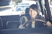 Smiling teenage girl driving car