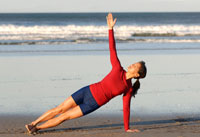 Asian woman in yoga pose on beach
