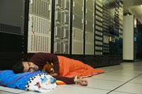 man sleeping on floor in computer room