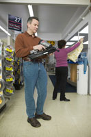 Man examining power tool in a store