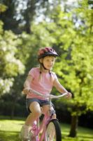 Young girl riding bicycle 11029004282| 写真素材・ストックフォト・画像・イラスト素材|アマナイメージズ