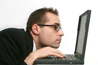 Hunched businessman using laptop