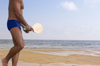 man on beach playing with paddle ball