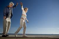Mature couple balancing on wall 11029004437| 写真素材・ストックフォト・画像・イラスト素材|アマナイメージズ