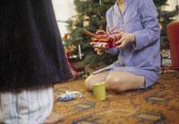 Couple on Christmas morning 11029004590| 写真素材・ストックフォト・画像・イラスト素材|アマナイメージズ