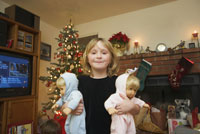 Young girl holding twin baby dolls