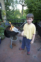 Young boy grilling in backyard
