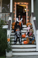 Children costumed for Halloween on porch