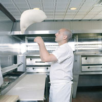 Cook tossing pizza dough