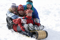 Family sledding down snowy hill