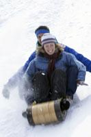 Couple sledding down snowy hill 11029005231| 写真素材・ストックフォト・画像・イラスト素材|アマナイメージズ
