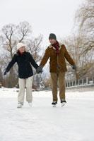 Couple ice skating hand-in-hand 11029005239| 写真素材・ストックフォト・画像・イラスト素材|アマナイメージズ