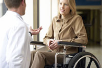Wheelchair-bound woman talking to doctor