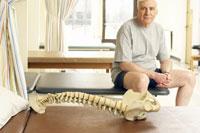 Skeleton sitting on pallet by man