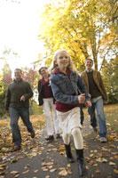 Family walking through park in autumn 11029005570| 写真素材・ストックフォト・画像・イラスト素材|アマナイメージズ
