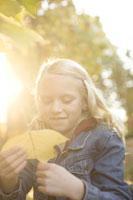 Girl outdoors holding autumn leaf 11029005578| 写真素材・ストックフォト・画像・イラスト素材|アマナイメージズ