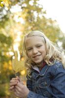 Girl outdoors holding autumn leaf 11029005580| 写真素材・ストックフォト・画像・イラスト素材|アマナイメージズ