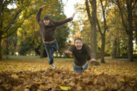 Two brothers jumping into autumn leaves