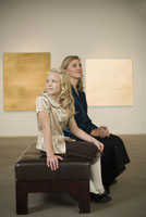 Mother and daughter sitting in gallery
