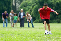 boy with soccer ball as family watches