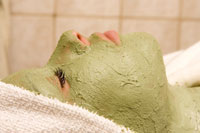 Close-up of woman with green facial mask