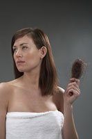 Woman holding a hairbrush full of hair
