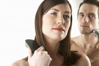Woman brushing her hair and man shaving