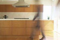 Blurred  man walking through kitchen